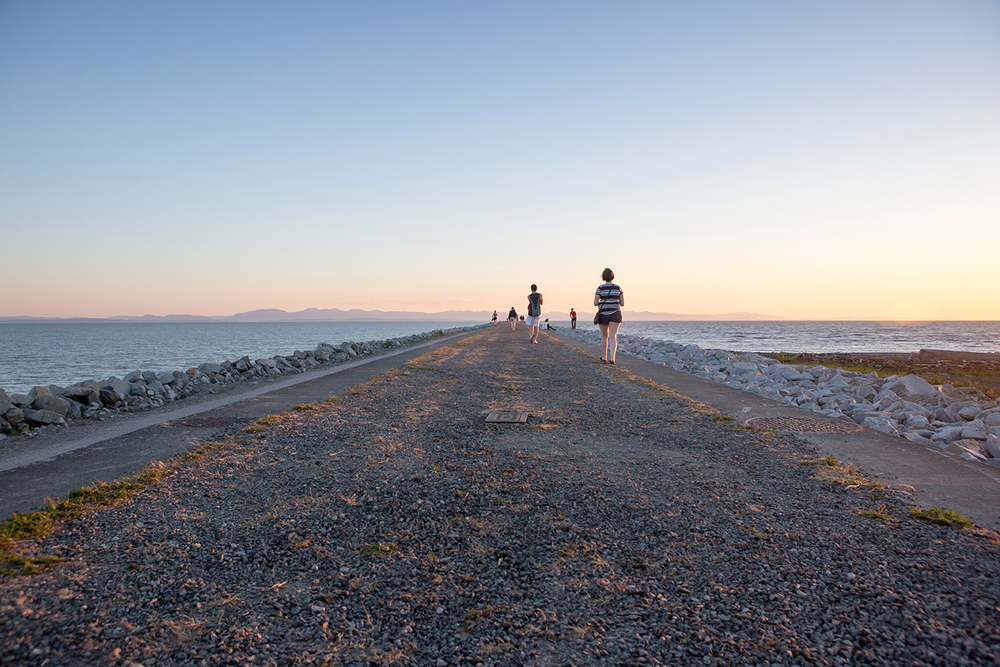 Several people walking along the gravel trail of the Iona Jetty at Iona Beach Regional Park.