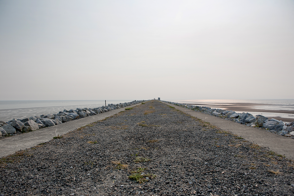 The gravel trail of the Iona Jetty on a very hazy, grey day at Iona Beach Regional Park.