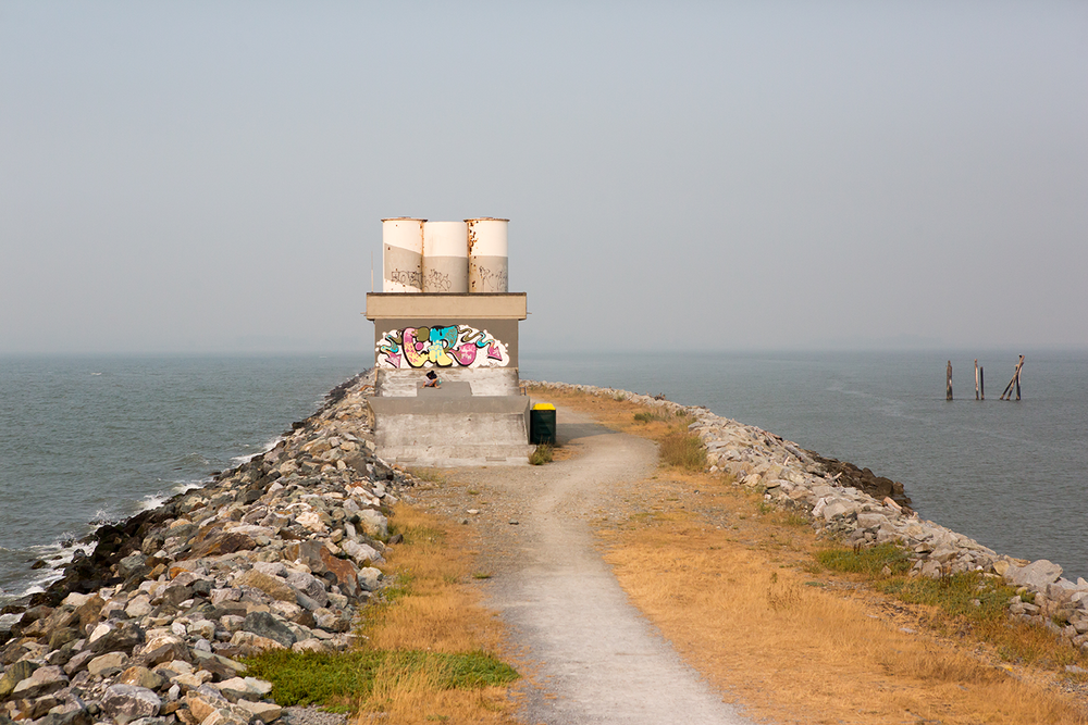A sewer facility with colorful graffiti situated at the end of the Iona Jetty at Iona Beach Regional Park.