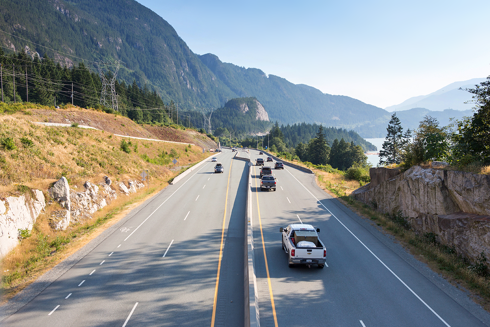 A scenic, coastal highway view with a mountain backdrop captured along British Columbia Highway 99.