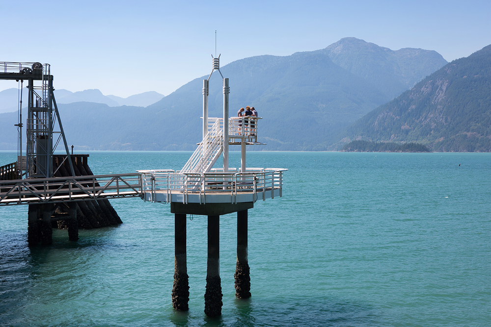 A seaside pier overlooking scenic mountains and clean, blue water at Porteau Cove Provincial Park.