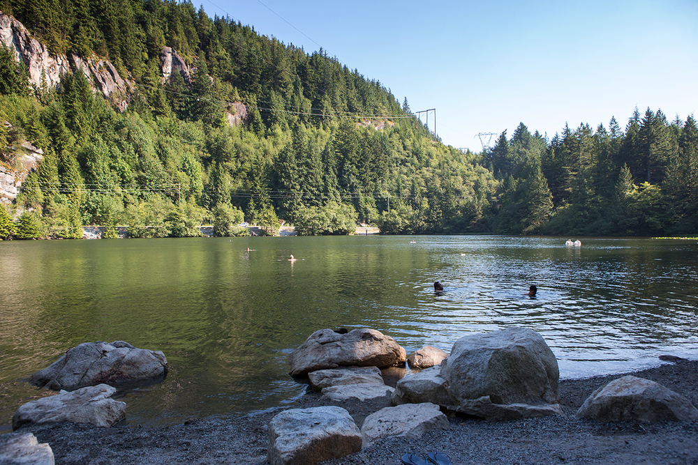 A scenic lakeside view with people swimming at Browning Lake near Vancouver, Canada.