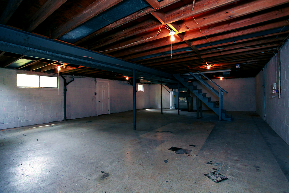 A creepy unfinished basement with a cement floor, wood beam ceiling, and eerie single bulb lighting.
