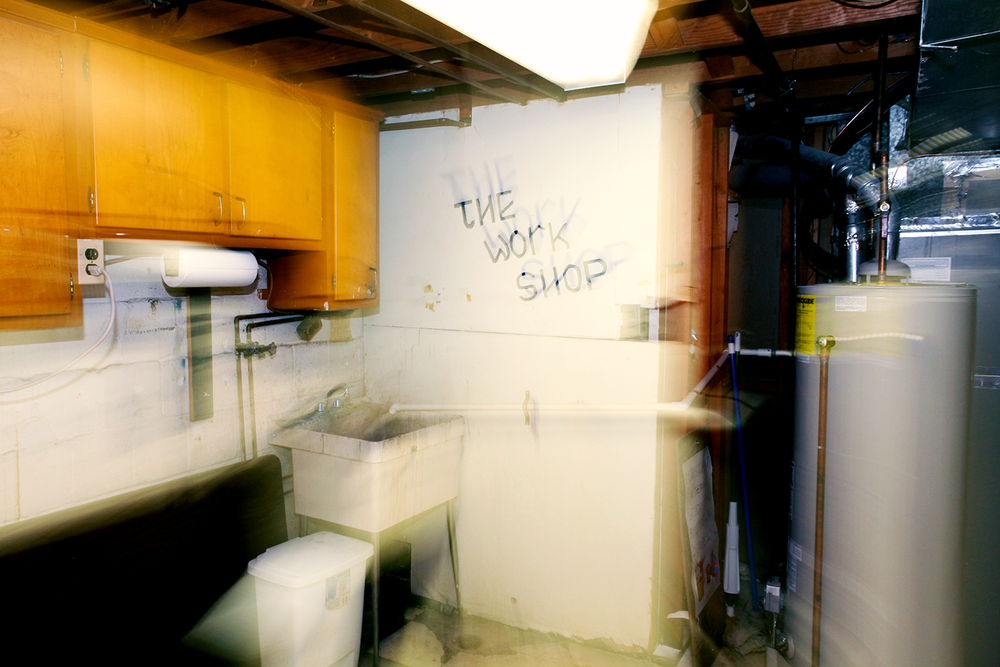 "A scary basement work room with the words ""the work shop"" written creepily on the wall."