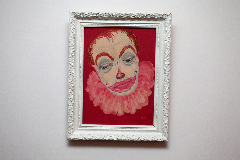 A crooked painting of a creepy, sad clown wearing red makeup and frowning.
