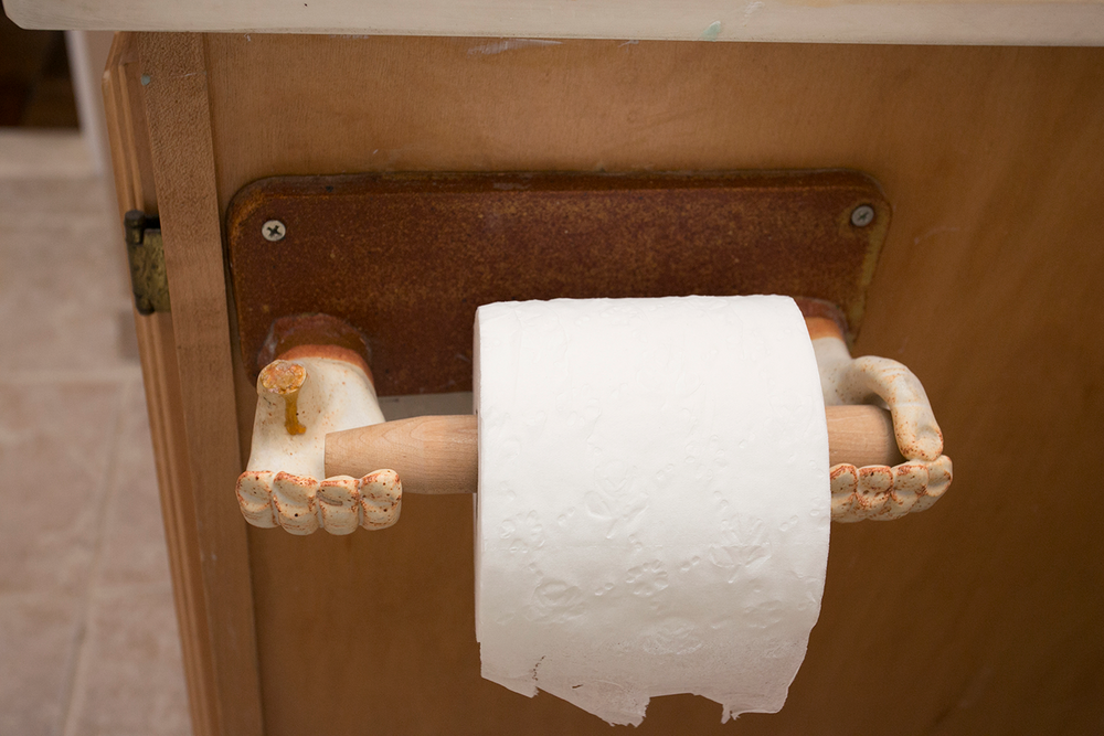 An eerie and unusual toilet paper holder with small hands.