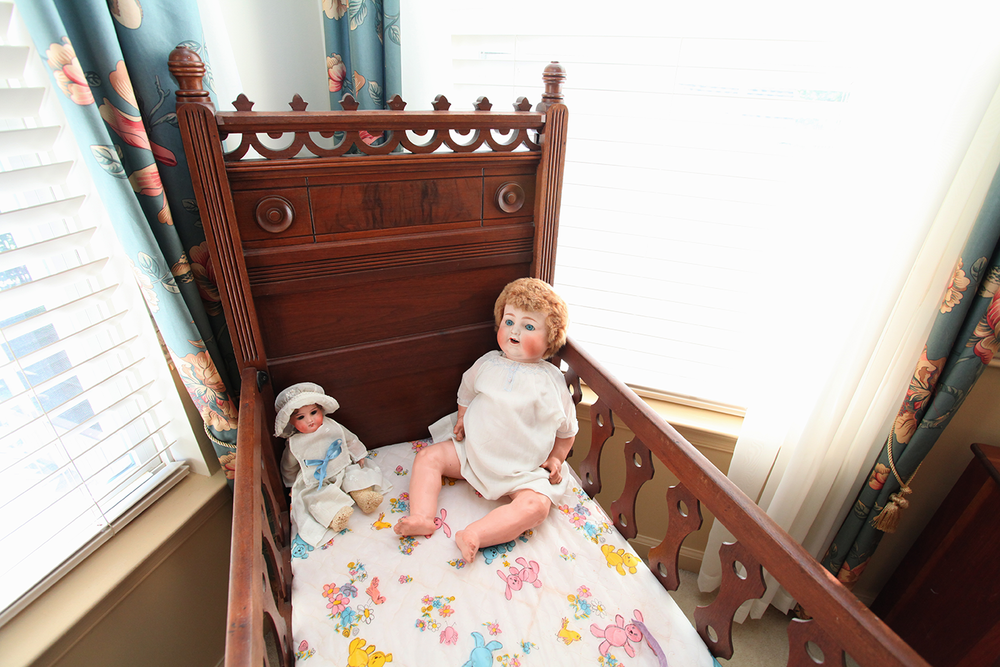 Two creepy, early century dolls eerily smiling and sitting together in a crib.