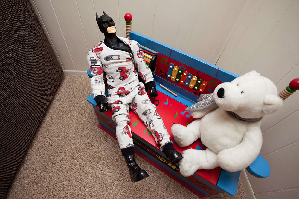 A funny batman doll dressed in car pajamas and sitting next to a white teddy bear.