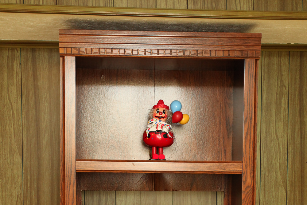 A creepy, red and white clown with balloons sitting on a wooden shelf and smiling.