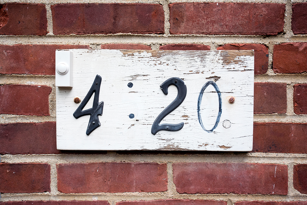 A house address sign with the number '420' hanging against a brick wall.