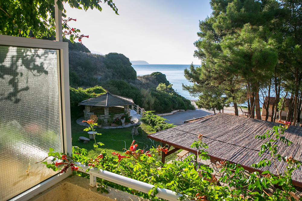 Balcony view of the Ionian Sea with stunning green wild life and rocky cliffs in Kefalonia, Greece.