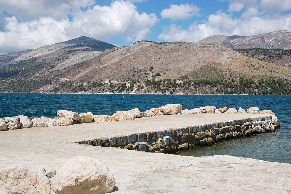 Beautiful landscape of a white stone pier, mountains, and still blue waters on the island of Kefalonia, Greece.