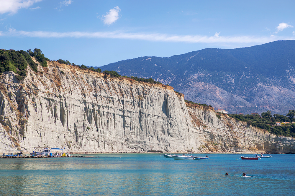 Beautiful seascape of a large, rocky cliff face and crystal clear waters on a sunny day in Kefalonia, Greece.