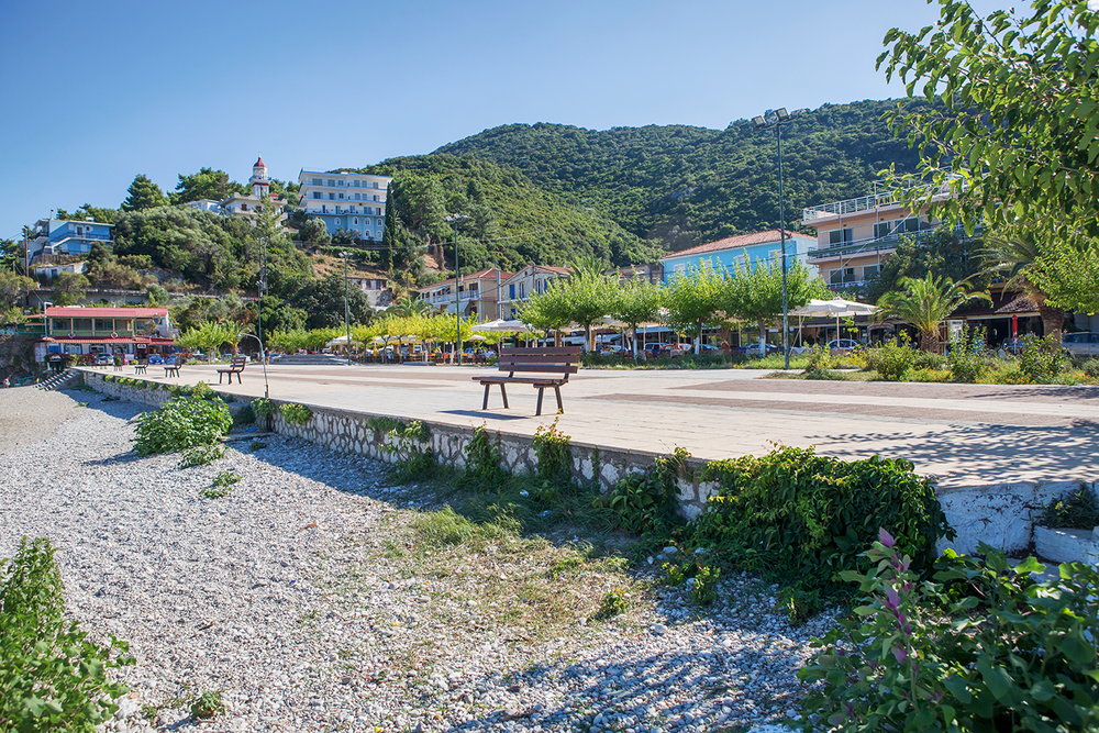 Wide angle landscape of a white, stony beach and the colorful village buildings of Poros on a sunny day in Kefalonia, Greece.