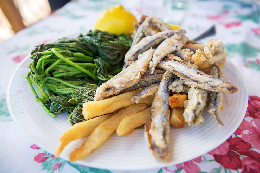 Close up of a delicious fried fish dish, served with french fries and green vegetables in Kefalonia, Greece.