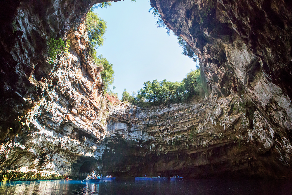 Wide angle landscape of the inside of Melissani Lake showing a massive cliff opening and boats floating on top of deep brackish waters.