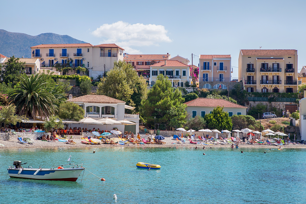 A colorful beach landscape with numerous sun bathers and crystal clear blue water, against a backdrop of Assos Village in Kefalonia, Greece.