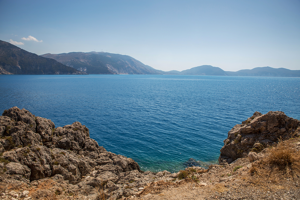 A vast wide angle landscape showing open blue waters and numerous rocky cliffs on a sunny day in Kefalonia, Greece.