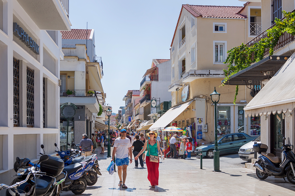 A busy market scene in the middle of Argostoli, Kefalonia showing several tourists browsing local shops.