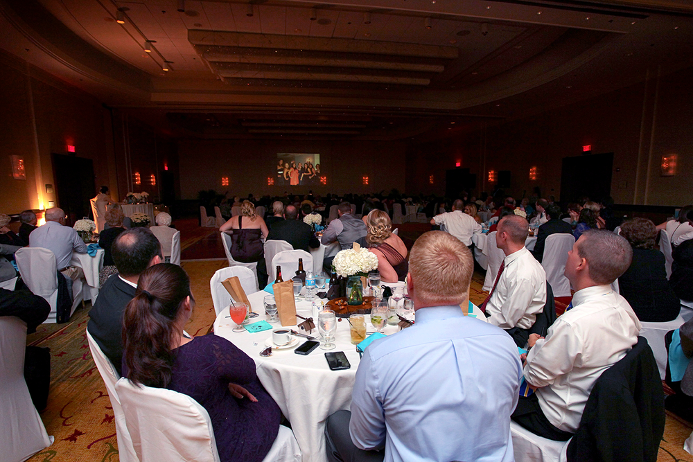 A dark wedding reception venue with several guests watching a wall projection of old images.