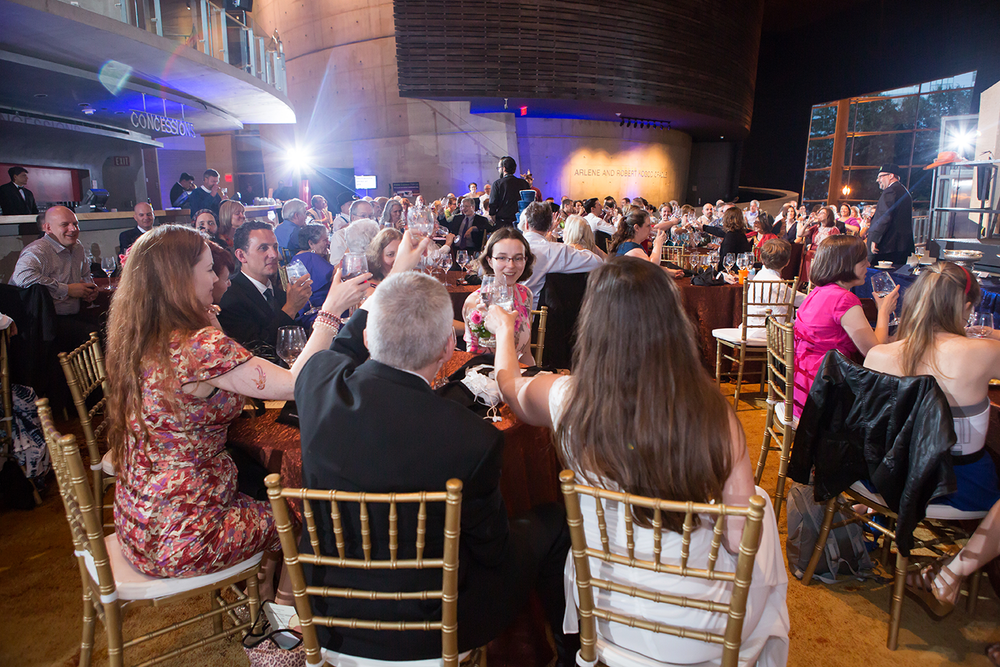 A large wedding reception venue being lit by multiple remote flashes as several guests toast a speaker.
