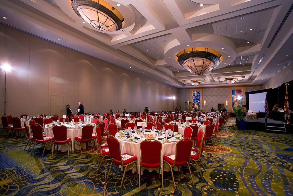 Large reception room with high ceiling, white tables, and red chairs being evenly lit by several remote flashes.