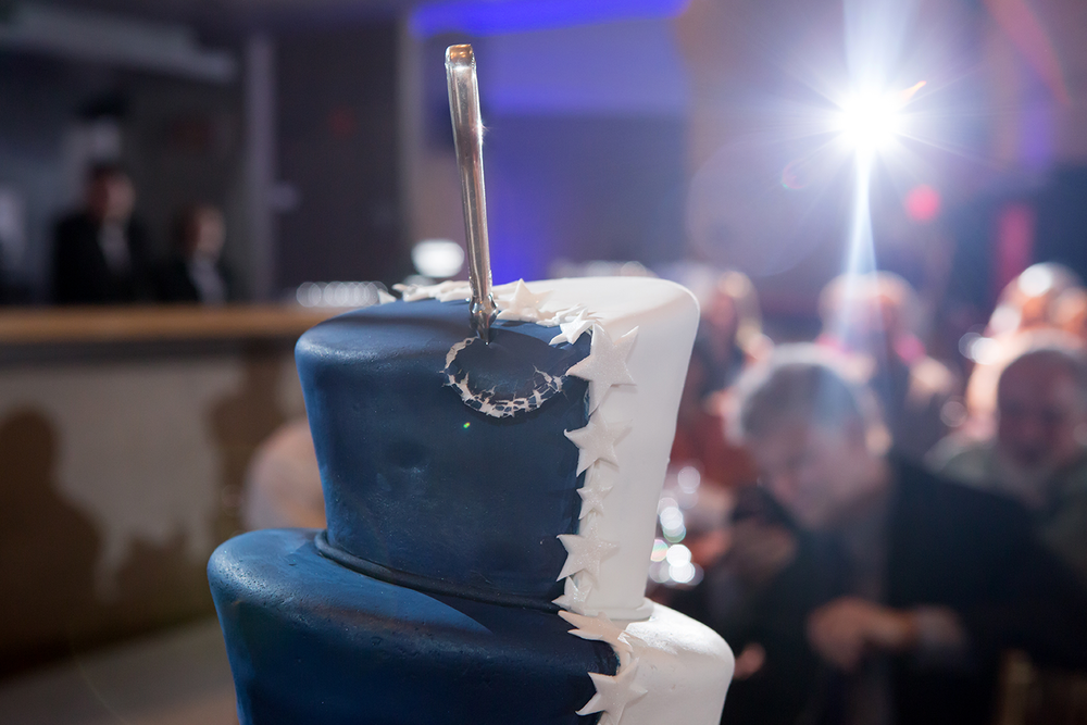 A blue and white wedding cake being back lit by a remote flash while guests are seen in the background.