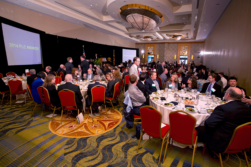 Guests of a corporate award ceremony seen mingling in a large reception hall being lit by several remote flashes.