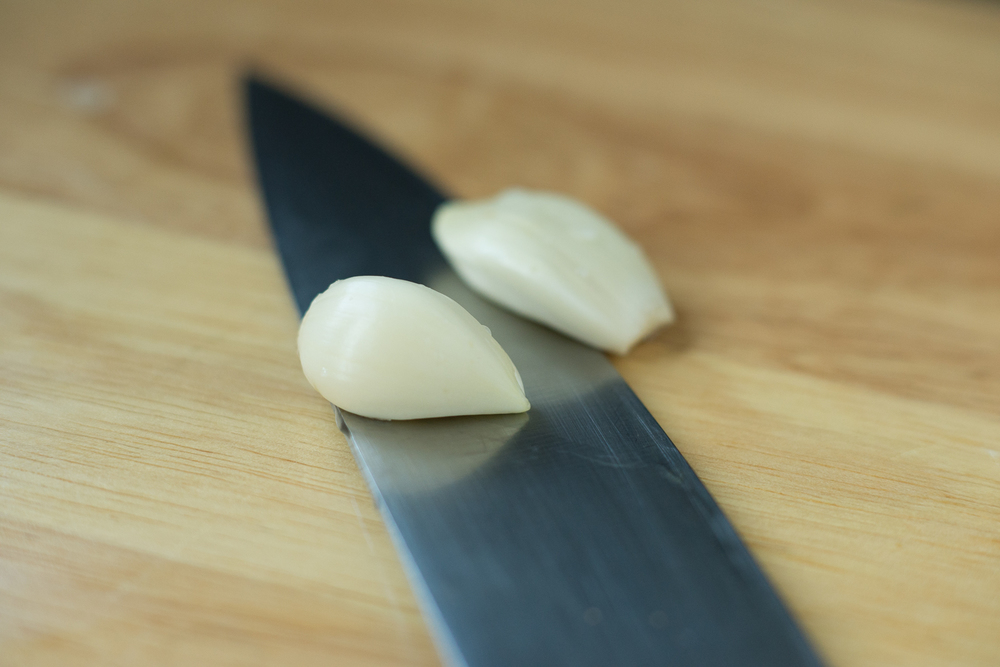 Use the flat side of your knife to smash the garlic cloves to remove the outer shell.