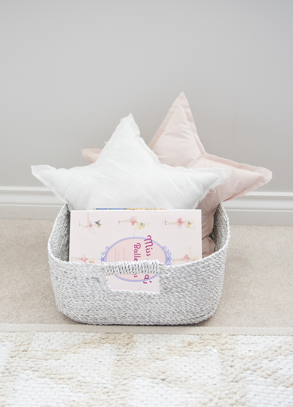 star pillows and books in silver basket