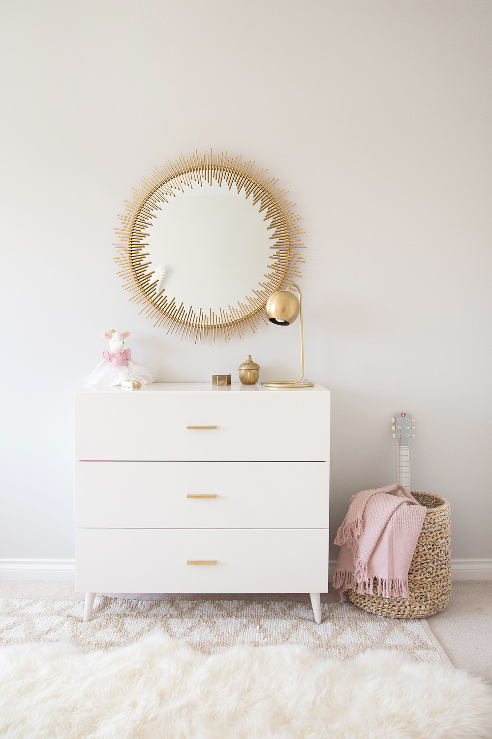 gold statement mirror above mid century modern dresser in a kids room