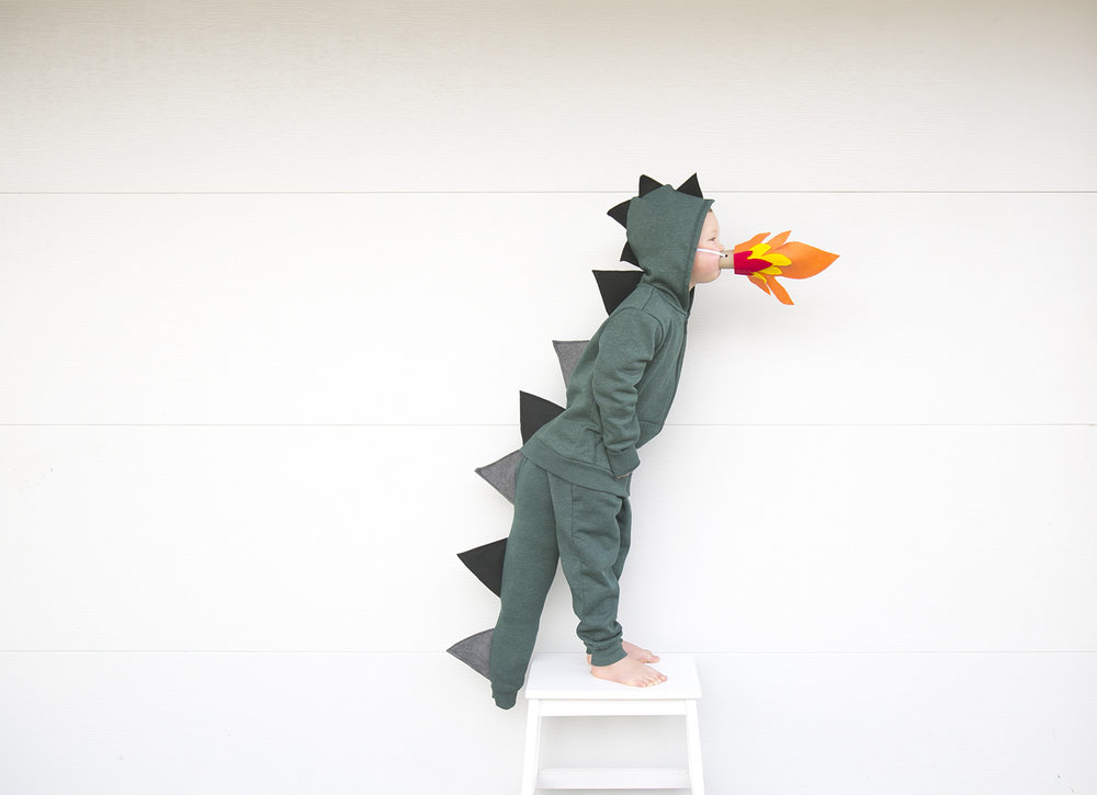 boy dressed up as green dragon with fiery breath for halloween