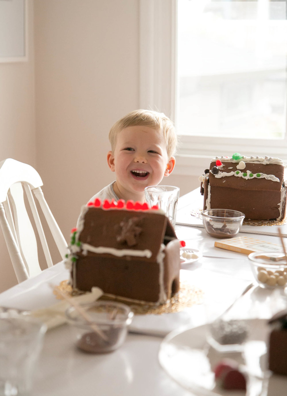 toddler smiles with gingerbread house