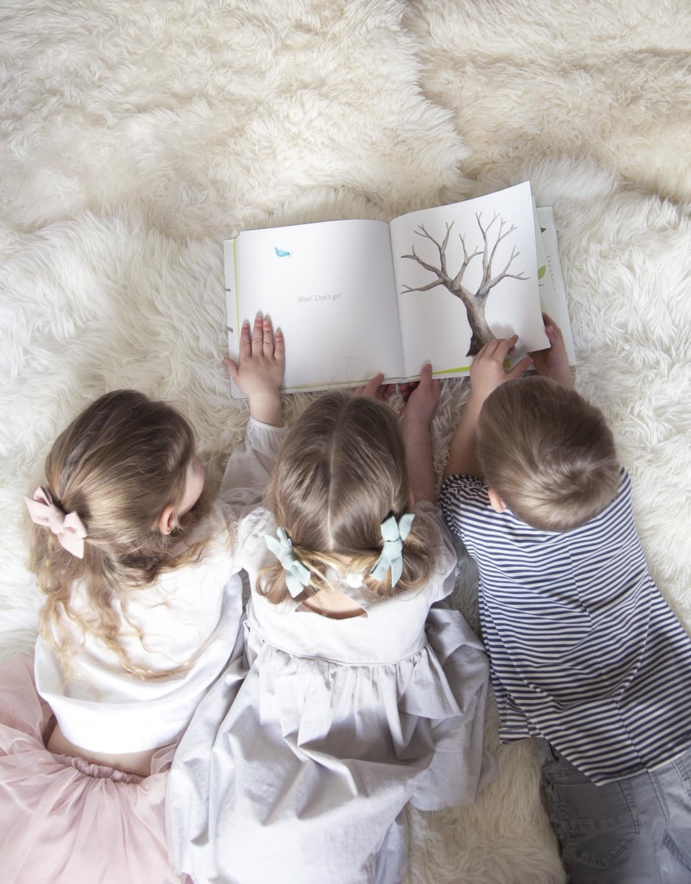 Kids reading Tap the Magic Tree together