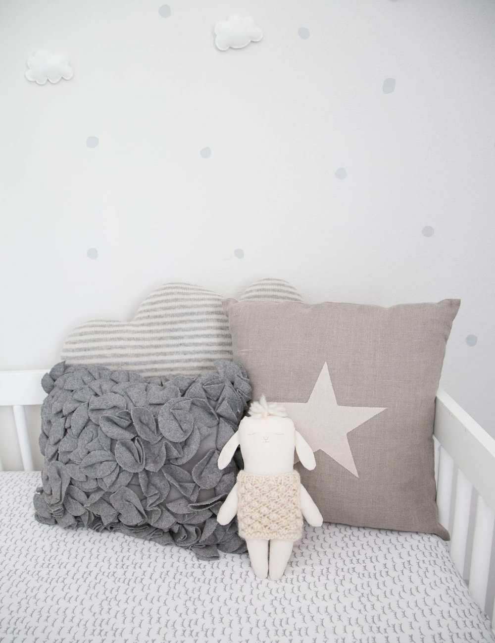 Neutral nursery with pillows in crib