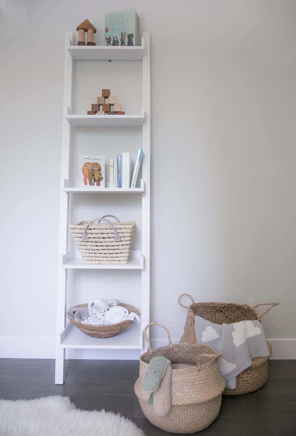 A simple white ladder shelf in a children's room