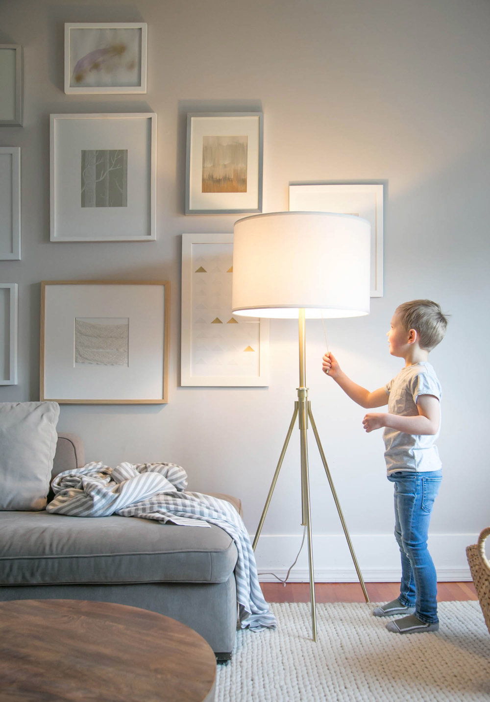 boy turning on living room lamp