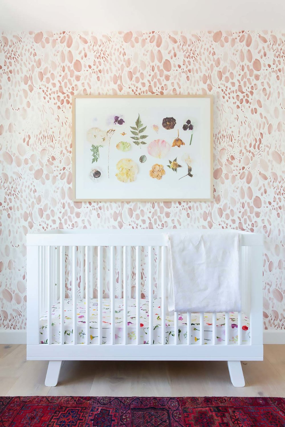 pressed flower art above crib in baby nursery