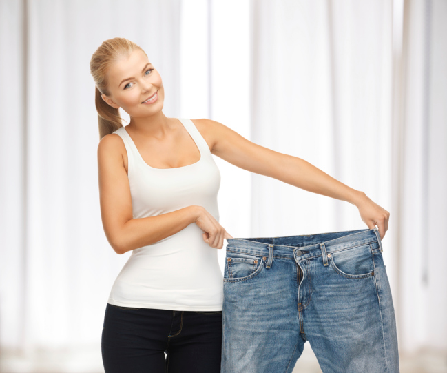 Fit woman demonstrating bigger size jeans