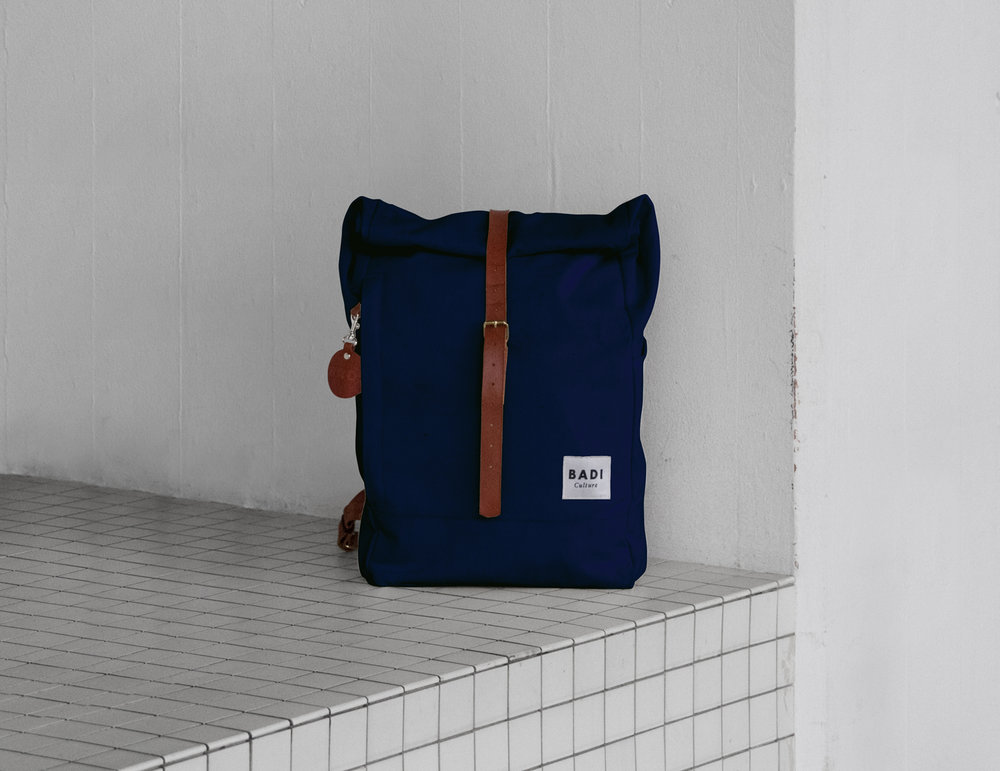 The Roll-Over backpack in navy with brown leather