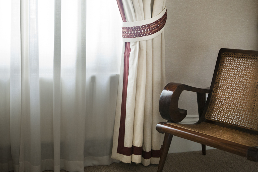 Pelmeted curtains with a cranberry border and passementerie are set in front of a wool sheer curtain