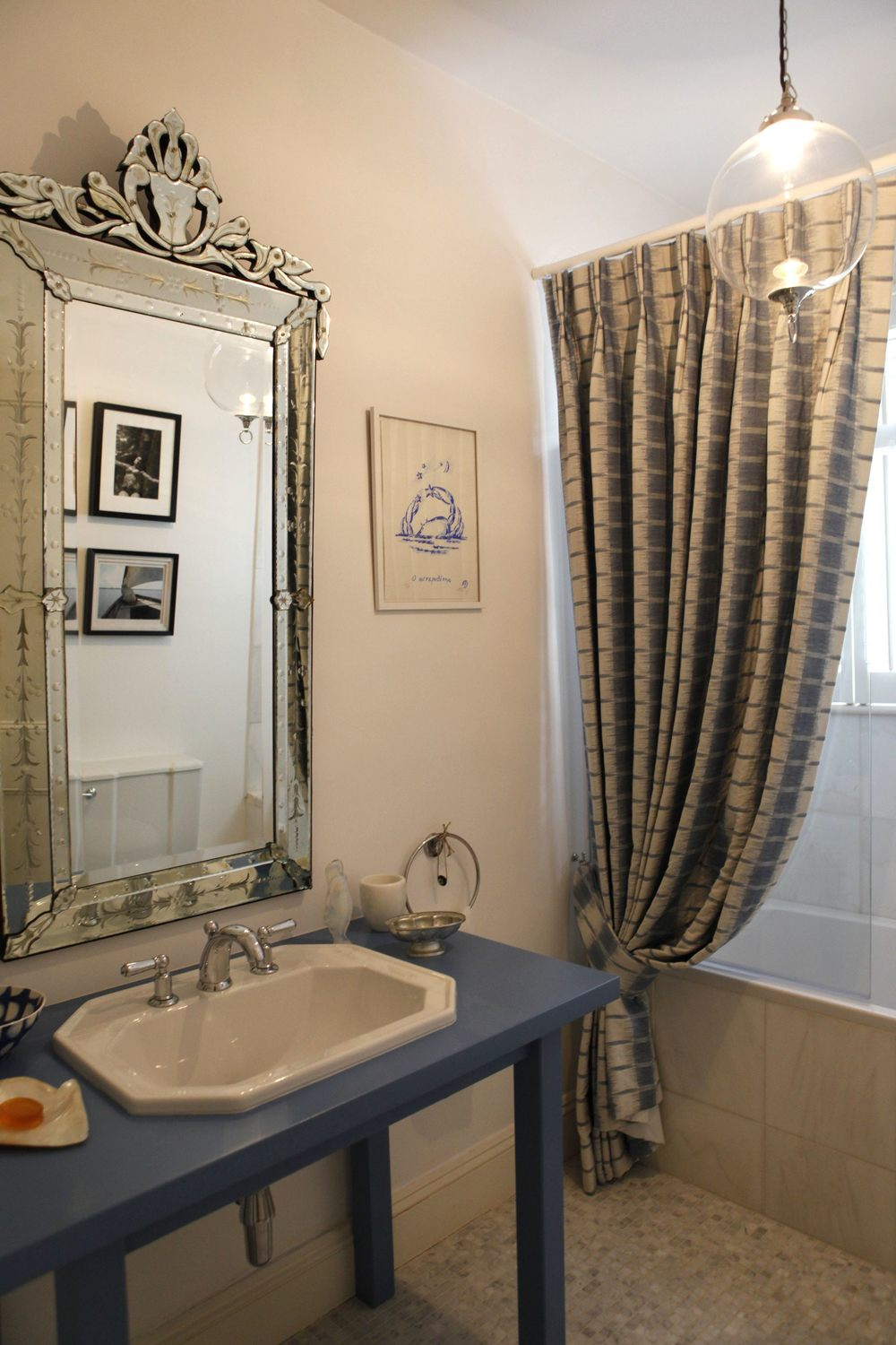Bathroom in marble and Mykonos blue with hand woven linen curtain