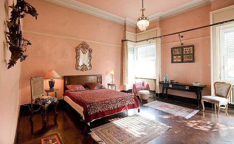 The terracotta walls, the dappled light and sparse furniture makes this an infinitely relaxing bedroom