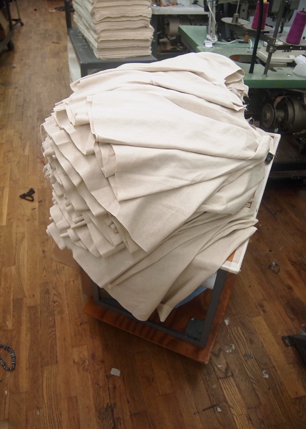 A stack of  sewn skirt pieces awaits waistband attachment.