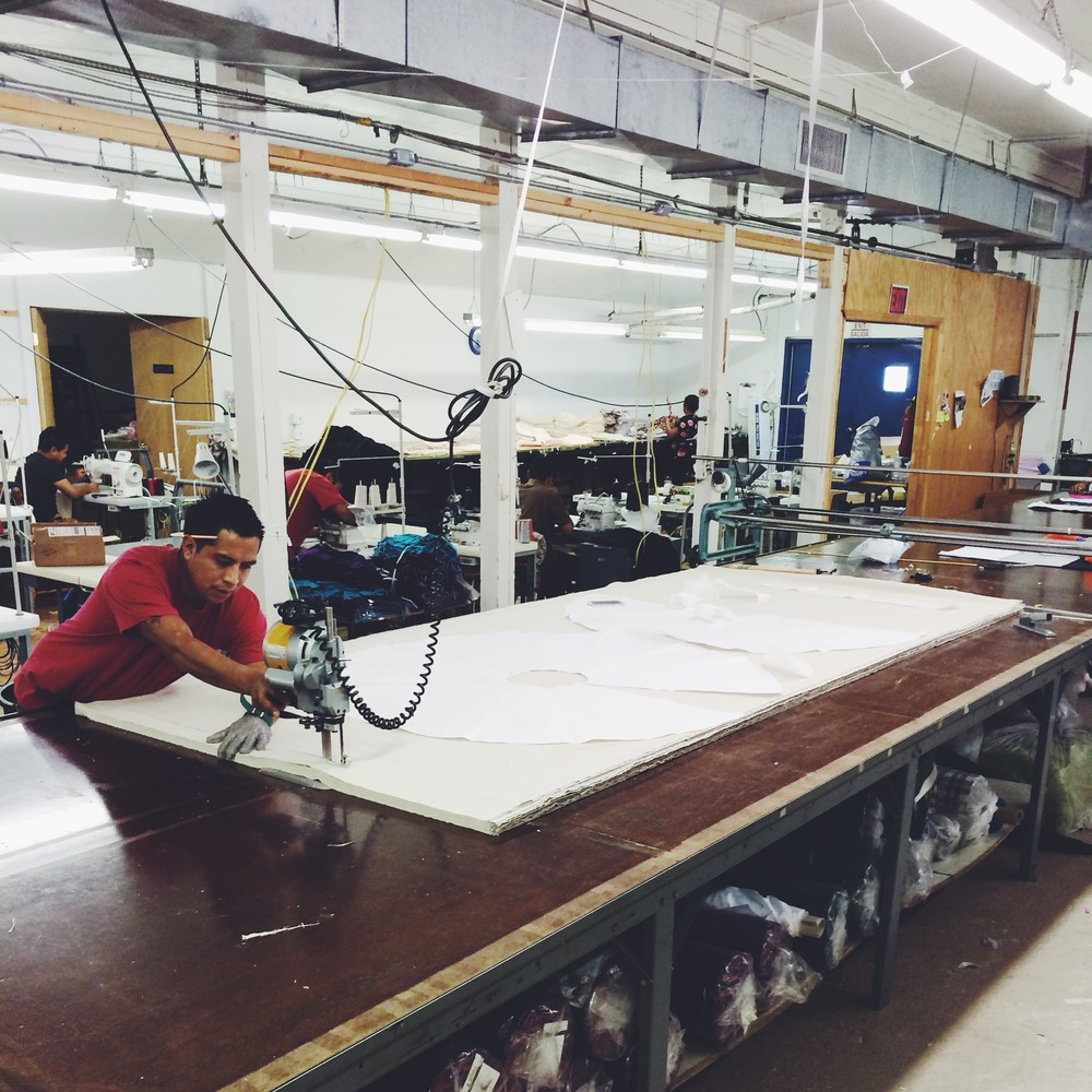 A skilled cutter slices through 80+ layers of fabric to cut our skirt pieces.