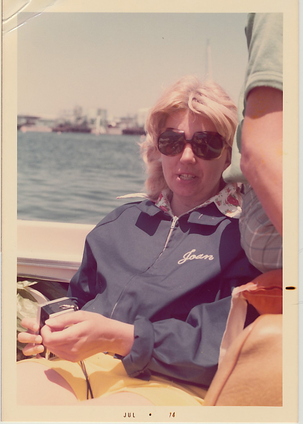 Joan wearing her boating jacket and holding a camera.