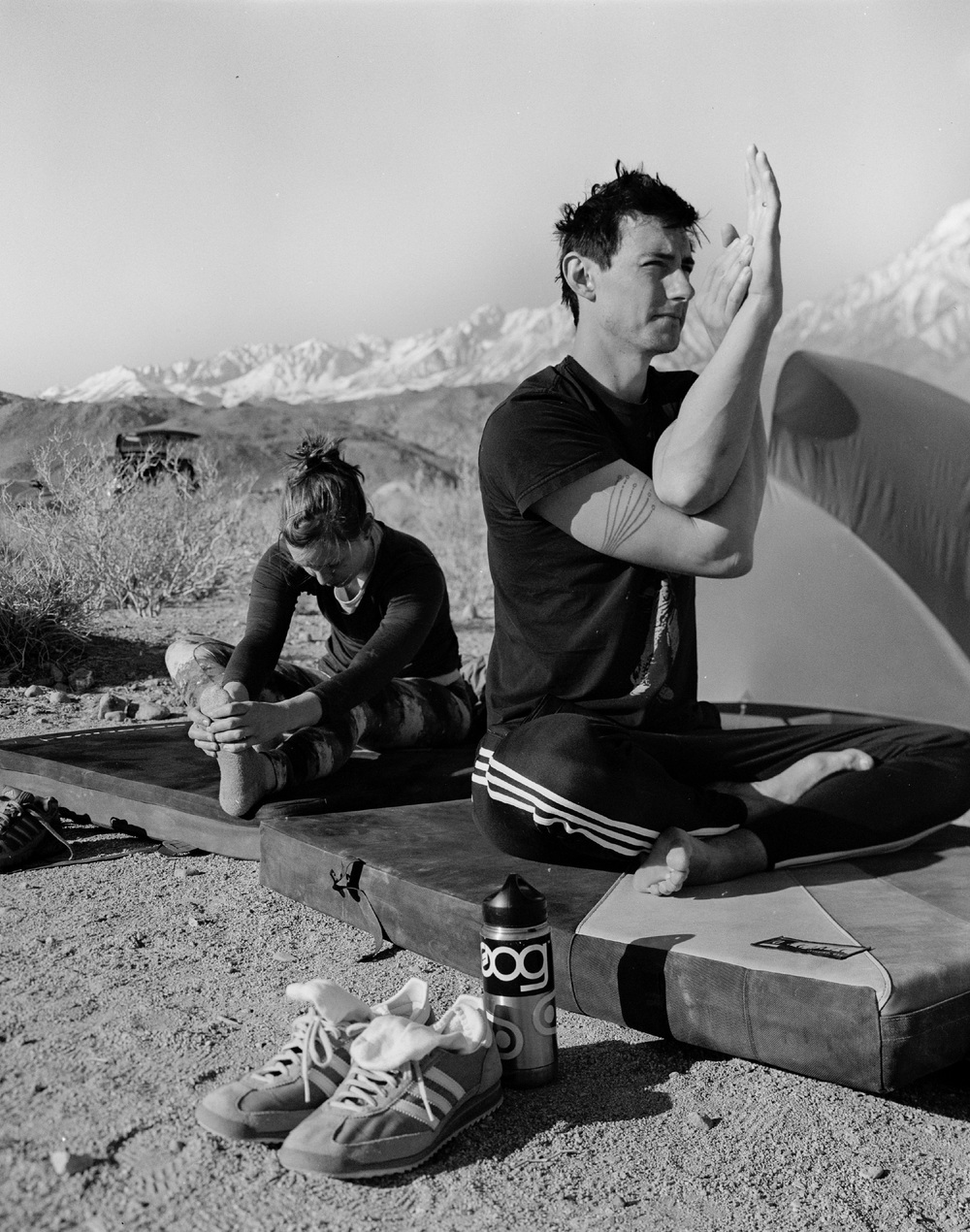 Lauren and Erik in the midst of a stretch and yoga session at our campground, with mountains looming in the background.
