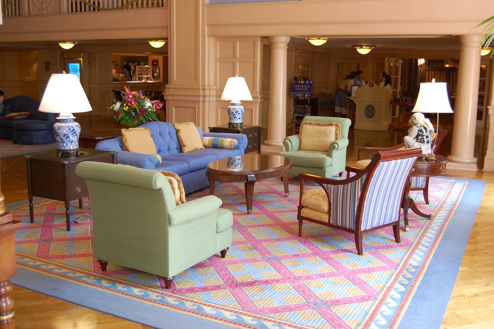 Enjoy a pleasant visit with friends or family in this seating area in the lobby of Disney's Yacht Club Resort - Disney World.