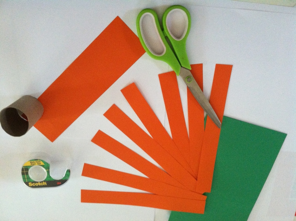 Supplies to make a Mickey Mouse Paper Jack-O-Lantern: Orange construction paper, green construction paper, a toilet paper tube, scissors and transparent tape,or craft glue or a glue gun.