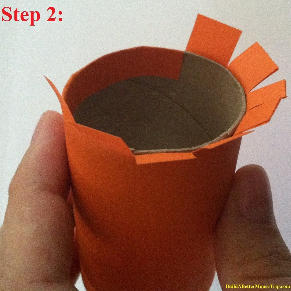 Cover a toilet paper tube with orange construction paper.   Cut slits in the paper that extends past the ends of the tube, fold extra length over and attach to the inside of the tube using tape, craft glue,  or a glue gun.
